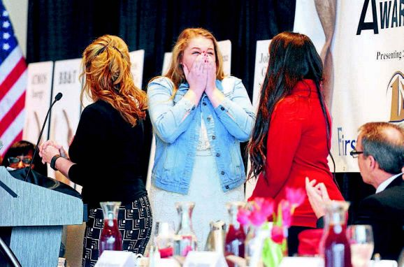 Addysanne Stout of Henderson County High School, center, reacts along with Angel Phillabaum of Daviess County High School after they were each awarded a $20,000 scholarship from Girls Inc. at the Athena Awards Luncheon.
