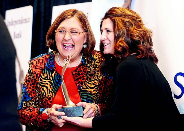 Aloma Dew, left, recipient of the 18th annual Athena Award, accepts the awardfrom Amy Jackson of First Security Bank at the annual awards luncheon Wednesday at the Owensboro Convention Center.